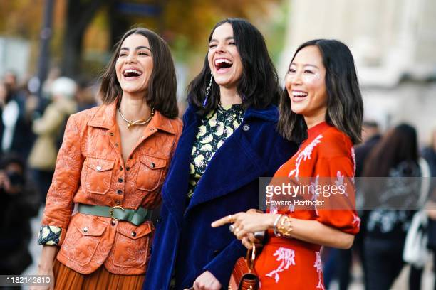 Camila Coelho wears a necklace, an orange quilted safari jacket, an almond-green belt, a rust-color flowing gathered and ruffled skirt ; Bruna...