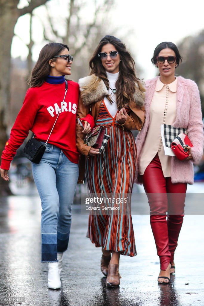 Camila Coelho (L) wears a red pull over with a blue turtleneck and the inscription 'Paris', a black bag, blue denim jeans pants, and white shoes, outside the Mashama show, during Paris Fashion Week Womenswear Fall/Winter 2017/2018, on March 5, 2017 in Paris, France.
