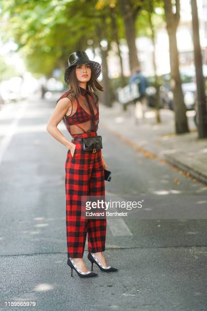 Camila Coelho wears a shiny black Dior hat a transparent black top a red checkered Dior bra red checkered Dior pants a black Dior belt bag black Dior...