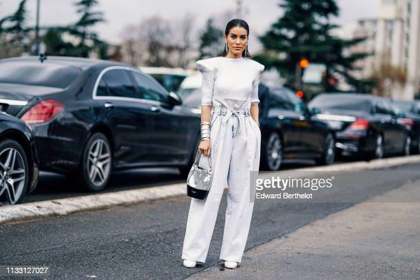 Camila Coelho wears a silver top with shoulder pads white flared pants a Balmain bag white shoes outside Balmain during Paris Fashion Week Womenswear...