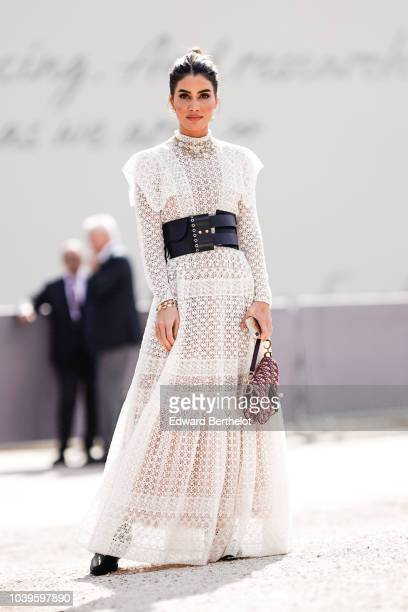 Camila Coelho wears a white lace mesh dress a Dior Saddle bag and a corset outside Dior during Paris Fashion Week Womenswear Spring/Summer 2019 on...