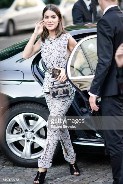 Camila Coelho wears a white lace sleeveless top white lace pants black shoes and a rectangular Vuitton bag outside the Vogue Foundation Dinner during...