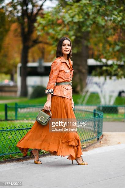 Camila Coelho wears an orange jacket with embroidered flowers patterns, a green khaki belt, a Chloe bag, pleated asymmetric long skirt, shoes, a...