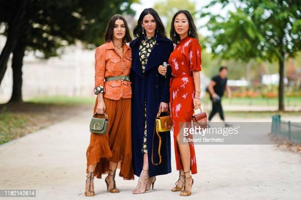 Camila Coelho wears earrings, a necklace, an orange quilted safari jacket, an almond-green belt, an almond-green crocodile pattern Chloe handbag, a...