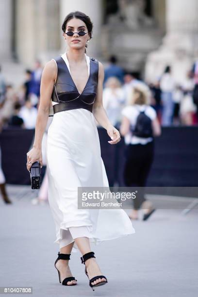 Camila Coelho wears sunglasses a black leather low neck top a white dress heels shoes a Vuitton rectangular clutch outside the Ralph Russo show...