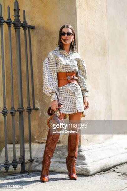 Camila Coelho wears sunglasses, a brown leather corset, a dress with printed geometric patterns, a brown bag, brown leather high boots, outside the...