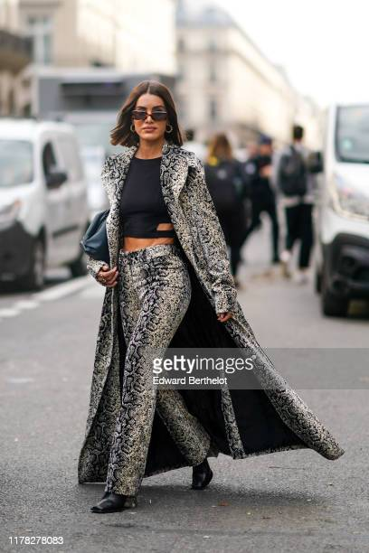 Camila Coelho wears sunglasses a snake print pattern long coat flare pants a cropped top earrings black shoes outside Giambattista Valli during Paris...