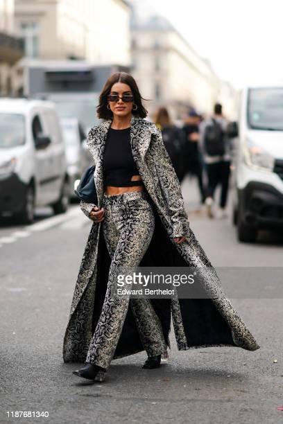 Camila Coelho wears sunglasses a snake print pattern long coat flare pants a cropped top earrings black shoes outside Giambattista Valli during Paris...