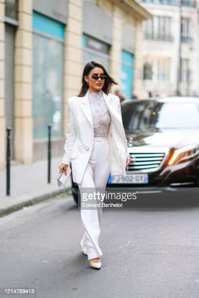 Camila Coelho wears sunglasses a white long blazer jacket a white lace mesh turtleneck top flared pants pointy shoes a clutch outside Ralph Russo...