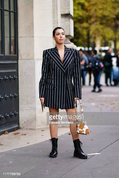Camila Coutinho wears an oversized blazer jacket printed dress, a brown cow hide bag, black leather boots, outside Elie Saab, during Paris Fashion...
