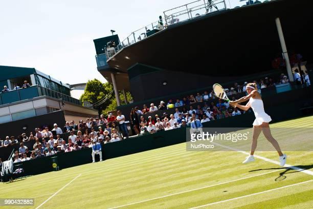 Camila Giorgi of Italy returns a shot from Anastasija Sevastova of Latvia in the first round of the 2018 Wimbledon Championships at the All England...
