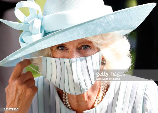 Camilla, Duchess of Cornwall adjusts her face mask as she attends day 1 of Royal Ascot at Ascot Racecourse on June 15, 2021 in Ascot, England.
