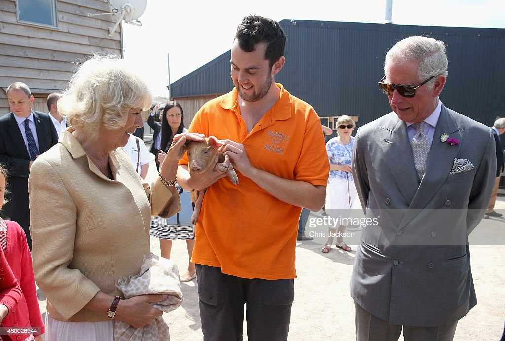 Camilla, Duchess of Cornwall and Prince Charles, Prince of Wales are shown a piglet as they visit Humble by Nature Farm on July 9 2015 in Monmouth, Wales. Humble by Nature is a working farm which was saved from closure by Kate Humble and her husband Ludo Graham in 2010. It includes a rural skills centre as well as a farm shop, cafe and adventure playground.