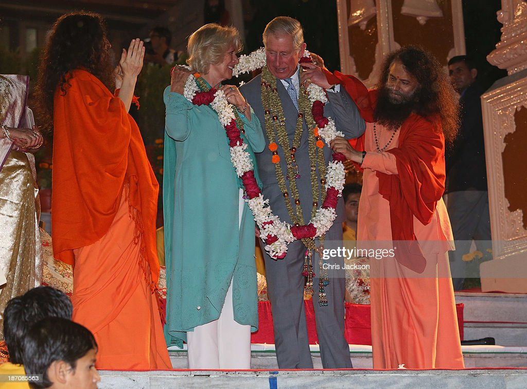 Camilla, Duchess of Cornwall and Prince Charles, Prince of Wales are presented with a large garland by Pujya Swami Chidanand Saraswatiji Maharaj as they take part in an Aarti ceremony at the Parmarth Niketan Temple on the banks of the River Ganges during day 1 of an official visit to India on November 6, 2013 in Dehradun, India. This will be the Royal couple's third official visit to India together and their most extensive yet, which will see them spending nine days in India and afterwards visiting Sri Lanka in order to attend the 2013 Commonwealth Heads of Government Meeting.