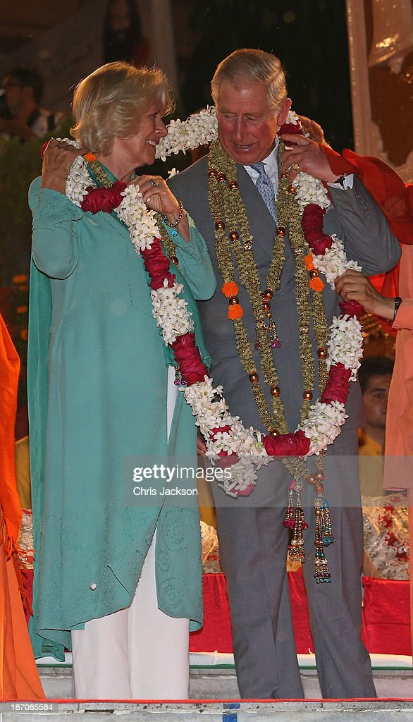 Camilla, Duchess of Cornwall and Prince Charles, Prince of Wales are presented with a large garland as they take part in an Aarti ceremony at the Parmarth Niketan Temple on the banks of the River Ganges during day 1 of an official visit to India on November 6, 2013 in Dehradun, India. This will be the Royal couple's third official visit to India together and their most extensive yet, which will see them spending nine days in India and afterwards visiting Sri Lanka in order to attend the 2013 Commonwealth Heads of Government Meeting.