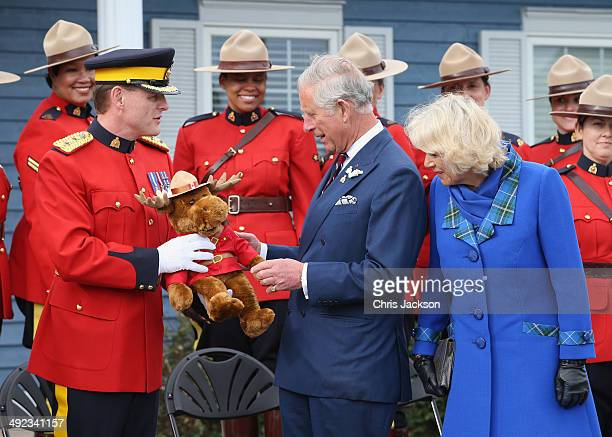 Camilla Duchess of Cornwall and Prince Charles Prince of Wales are presented with a toy moose by the Royal Canadian Mounted Police on May 19 2014 in...