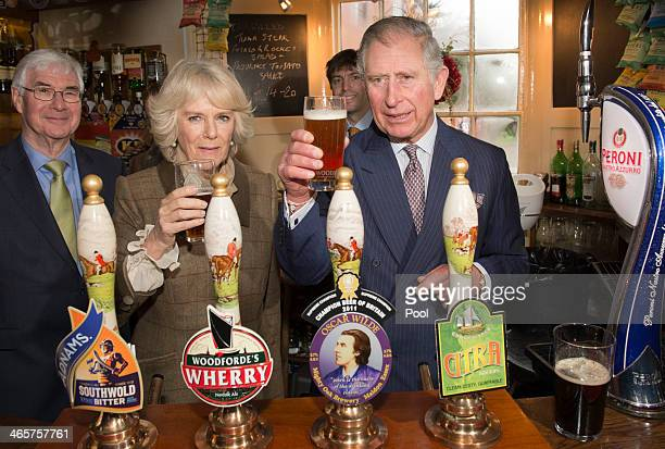 Camilla, Duchess of Cornwall and Prince Charles, Prince of Wales drink beer during a visit to 'The Bell' Pub during an official visit to Essex on...