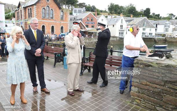 Camilla Duchess Of Cornwall and Prince Charles Prince Of Wales hold their ears as a small cannon is fired as they attend the Fowey Festival...