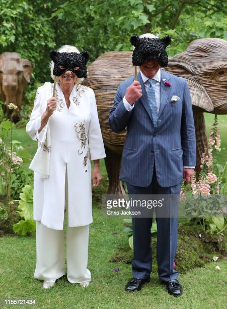 Camilla Duchess of Cornwall and Prince Charles Prince of Wales hold face masks as they host a reception for the Elephant Family Animal Ball at...