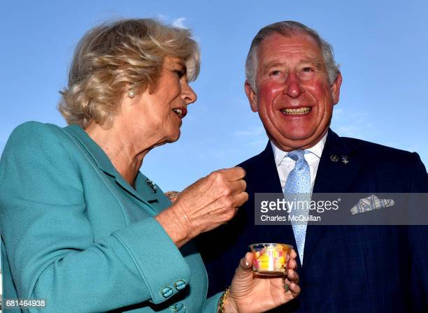Camilla Duchess of Cornwall and Prince Charles Prince of Wales laugh as they share an ice cream during their visit to the village market on May 10...
