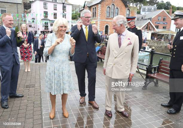 Camilla Duchess Of Cornwall and Prince Charles Prince Of Wales smile after a small cannon was fired to begin the Gig Club race at the Fowey Festival...
