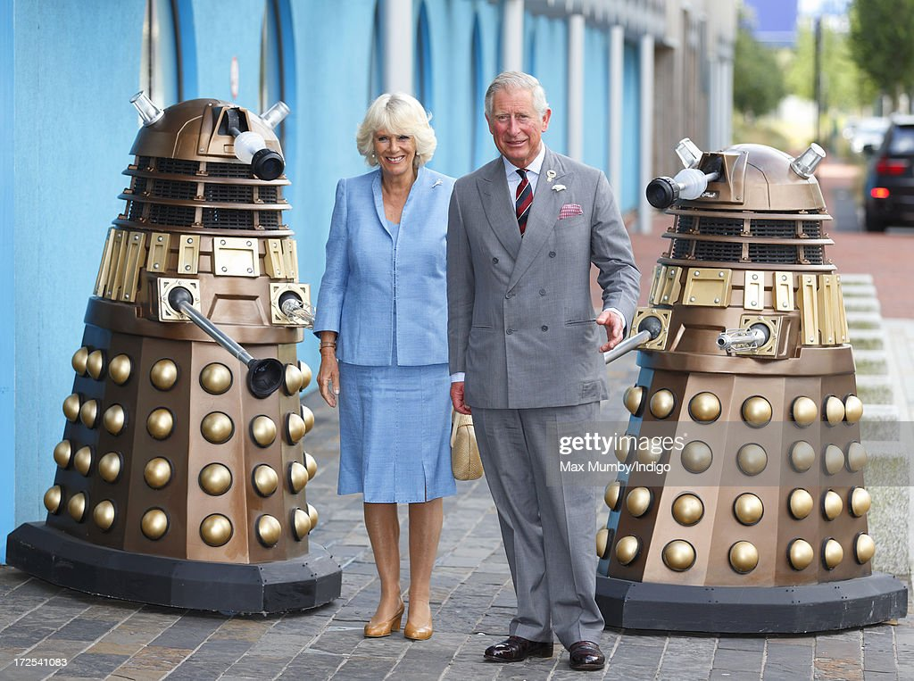 Camilla, Duchess of Cornwall and Prince Charles, Prince of Wales stand with two Daleks from the television series Doctor Who as they arrive for a visit to the BBC Roath Lock Studios on July 3, 2013 in Cardiff, Wales.