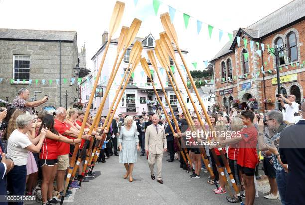 Camilla Duchess Of Cornwall and Prince Charles Prince Of Wales walk through a guard of honour by representatives from the Fowey Gig Club as they...