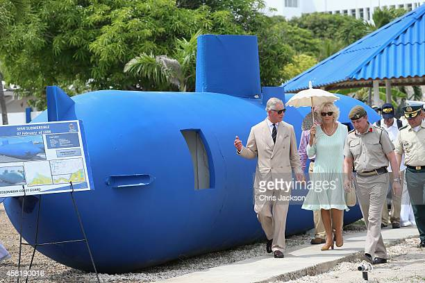 Camilla Duchess of Cornwall and Prince Charles Prince of Wales walk past a 'homemade' fibreglass drug smuggling submarine used to smuggle up to 2...