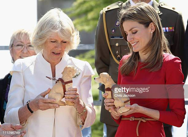 Camilla Duchess of Cornwall and Princess Letizia of Spain hold plastic guide dogs they were given as gifts during a visit to the Guide Dogs Center at...