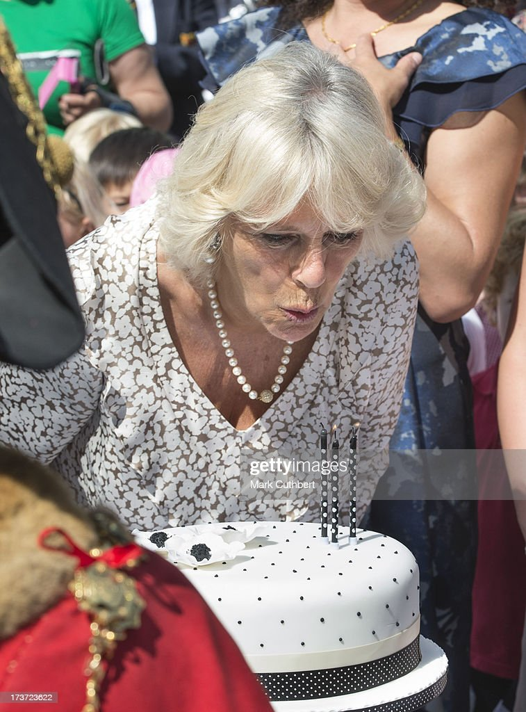 Camilla, Duchess of Cornwall, blows out the candles on a birthday cake to mark her 66th birthday, during a walkabout on a visit to Lostwithiel in Cornwall on July 17, 2013 United K.>>