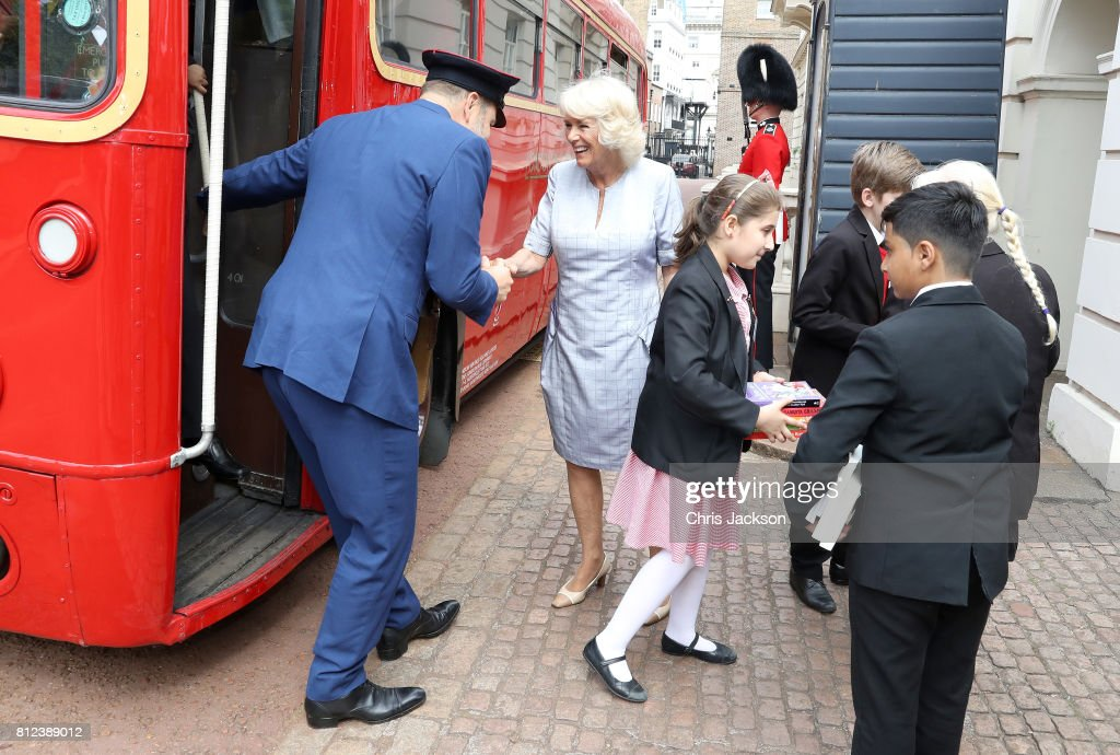 Camilla, Duchess of Cornwall greets comedian and author David Walliams, dressed as an bus conductor, as school children from Hemlington Hall Academy in Middlesbrough and Berkeley Primary School in Hounslow disembark a bus ahead of a tea party hosted by the Duchess of Cornwall to celebrate the Duchess's Bookshelves Project at Clarence House on July 11, 2017 in London, England. The Project is an initiative to find the nation's 70 favourite children's books to mark the Duchess of Cornwall's 70th birthday.