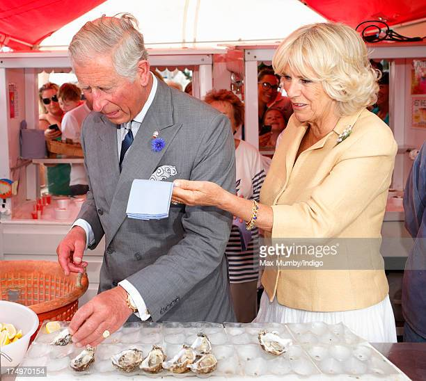 Camilla, Duchess of Cornwall hands Prince Charles, Prince of Wales some napkins to wipe his mouth as he eats an oyster whilst they visit the...