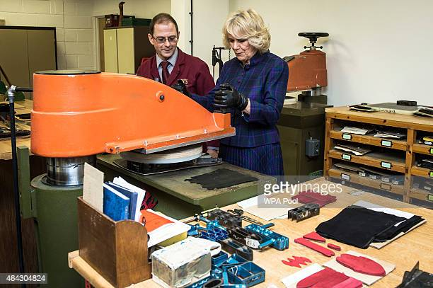 Camilla Duchess of Cornwall has a go at webbing to cut glove patterns from leather watched by Martin Clayton at Dents factory on February 24 2015 in...