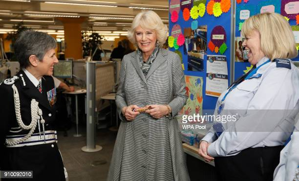 Camilla Duchess of Cornwall holds a chocolate bar after making a donation for a tuck shop charity as Metropolitan Police Commissioner Cressida Dick...