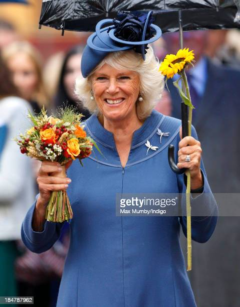 Camilla Duchess of Cornwall holds a posy of flowers as she shelters under an umbrella after attending The British Food Fortnight's Harvest Festival...