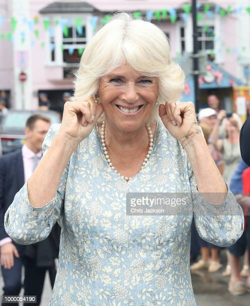 Camilla Duchess Of Cornwall holds her ears as a small cannon is fired as she attend the Fowey Festival Celebration with Prince Charles Prince Of...