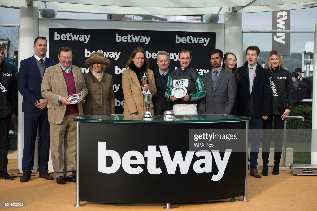 Camilla, Duchess of Cornwall Honorary Member of the Jockey Club, makes a presentation to the winners of The Betway Queen Mother Champion Steeple Chase, Winning Jockey Nico De Boinville on 'Altior', Winning Owner Patricia Pugh (C) and Winning Trainer Nicky Henderson (2nd L) as she attends the second day of The Festival, Ladies Day at Cheltenham Racecourse on March 14, 2018 in Cheltenham, England. The Duchess