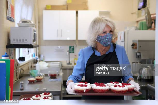 Camilla, Duchess of Cornwall, in her role as President of the Royal Voluntary Service, serves up a trifle dessert during a visit to The Royal...