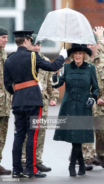 Camilla Duchess of Cornwall is handed an umbrella by an equerry as she inspects soldiers of 4th Battalion The Rifles during a homecoming parade of...