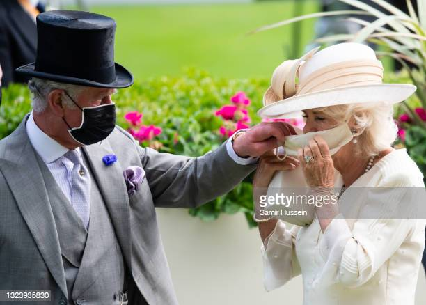 Camilla, Duchess of Cornwall is helped with her mask by Prince Charles, Prince of Wales attend Royal Ascot 2021 at Ascot Racecourse on June 16, 2021...