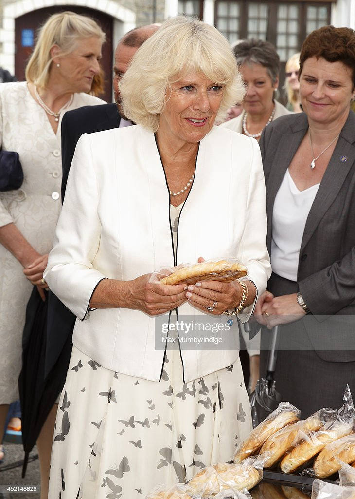 Camilla, Duchess of Cornwall is presented with a Cornish Pasty as she and Prince Charles, Prince of Wales tour a market on day one of their annual visit to Devon and Cornwall on July 14, 2014 in Looe, England.