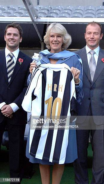 HRH Camilla Duchess of Cornwall is presented with a Newcastle United shirt and poses with Michael Owen and Alan Shearer during a visit to Newcastle...