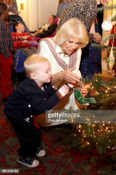Camilla Duchess of Cornwall is seen with a child from Helen Douglas House and Roald Dhal's Marvellous Children's Charity decorating the Clarence...