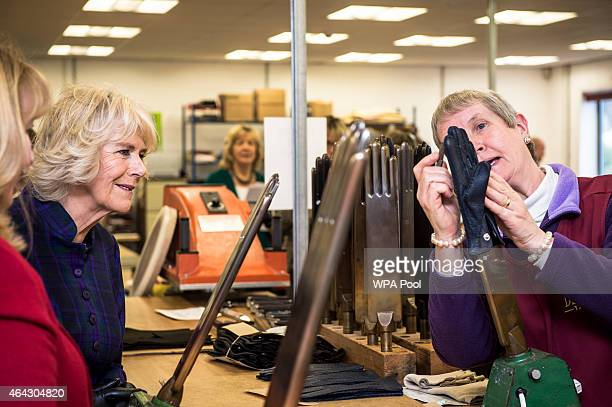 Camilla Duchess of Cornwall is shown a glove by Janet Jay at Dents factory on February 24 2015 in Warminster England
