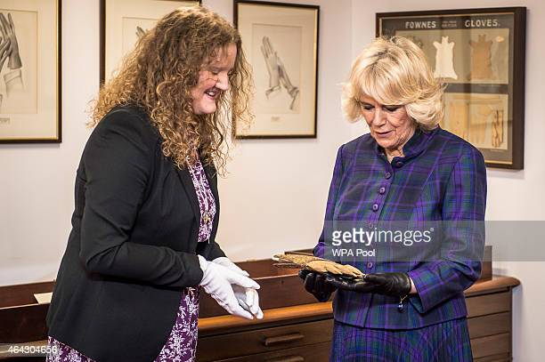Camilla Duchess of Cornwall is shown a pair of leather gloves worn by Sir Walter Raleigh by the museum curator Sarah Kenyon at Dents Fine Accessories...