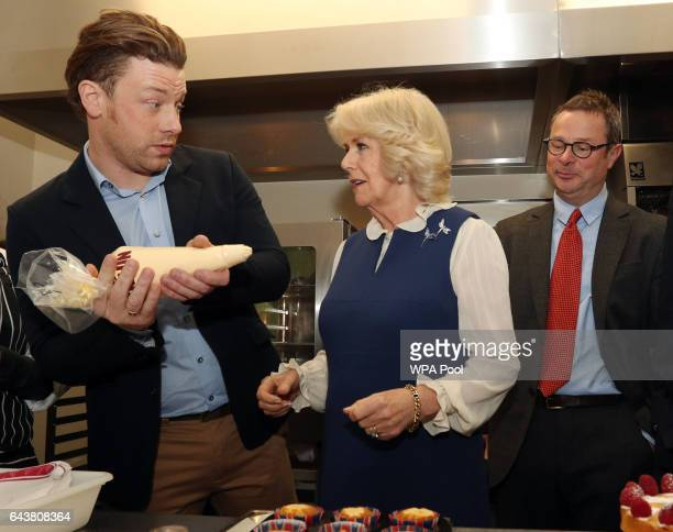 Camilla Duchess of Cornwall is shown how to use a piping bag by Jamie Oliver alongside Hugh FearnleyWhittingstall in the kitchen during a reception...