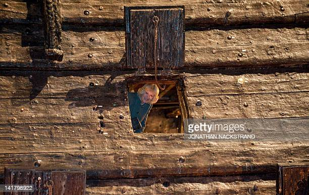 Camilla, Duchess of Cornwall, looks through a porthole on the Swedish warship Vasa at the Vasa Museum in Stockholm on March 24, 2012. Prince Charles...