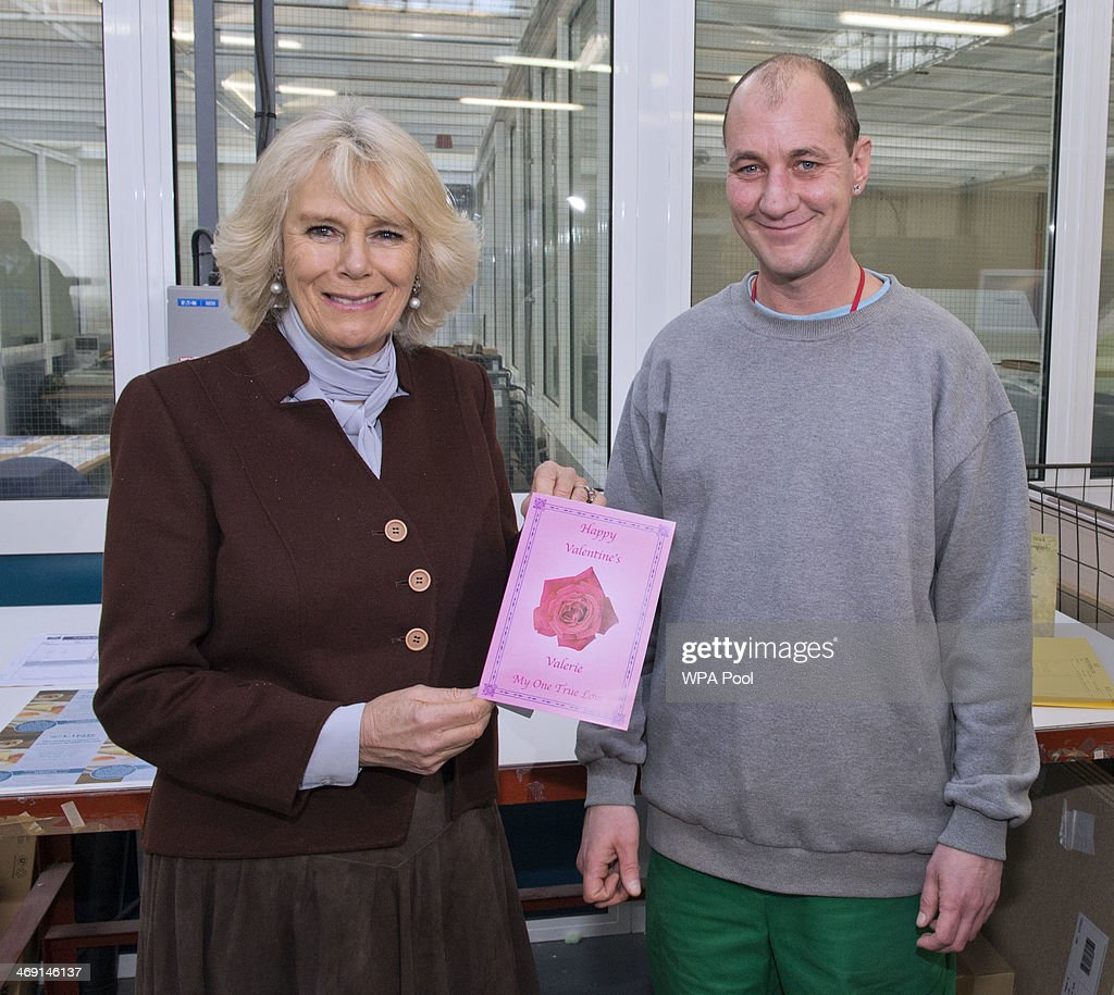 Camilla, Duchess of Cornwall poses with prisoner Gary Bird who presented her with a Valentine's Day card he printed in the prison print shop as she visits HM Prison Coldingley and met prisoners who have been taking part in schemes to improve literacy on February 13, 2014 in Woking, England. Her Royal Highness also toured the engineering and print workshops on her visit which provide on-site employment.