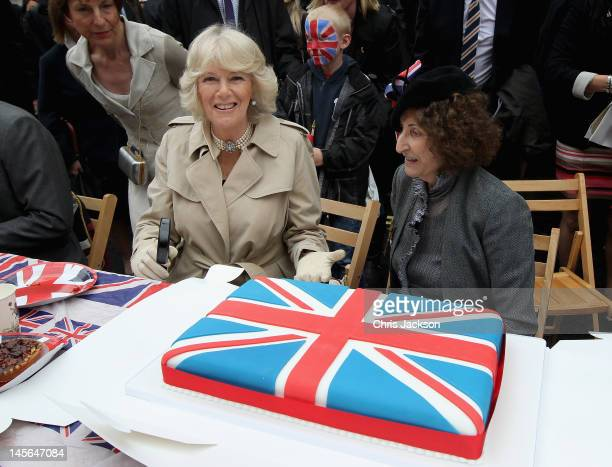 Camilla Duchess of Cornwall presents a Union Jack cake she bought as she attends the 'Big Jubilee Lunch' in Piccadilly ahead of the Diamond Jubilee...