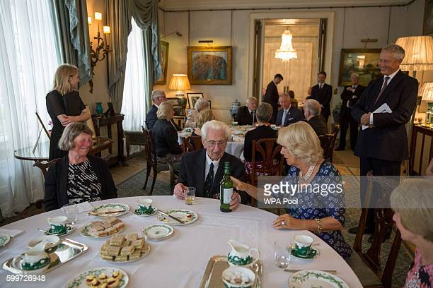 Camilla Duchess of Cornwall presents Flight Officer Ken Wilkinson with a bottle of Highgrove whiskey as they host a tea for veterans widows and...